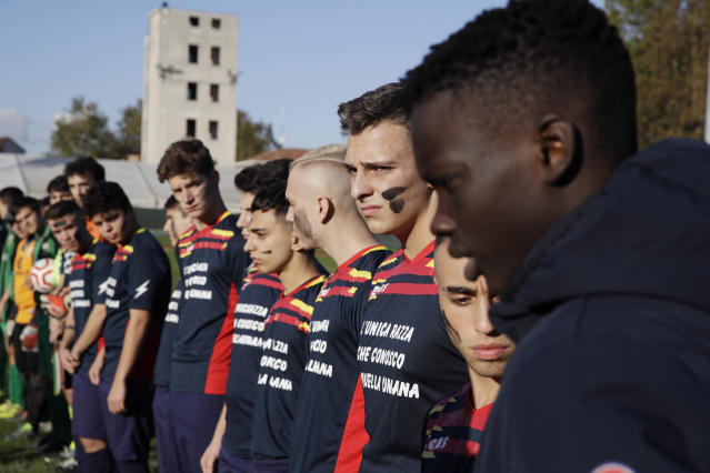 Desio players line up on the pitch with their faces painted with black marks as a symbolic sign against racism, prior to a youth team soccer match between Desio and Sovicese, at the municipal stadium in Desio, near Milan, Italy, Saturday, Nov. 9, 2019. The initiative comes a week after a 10-year-old member of the Aurora Desio team was allegedly subjected to racist abuse during a match. (AP Photo/Luca Bruno)