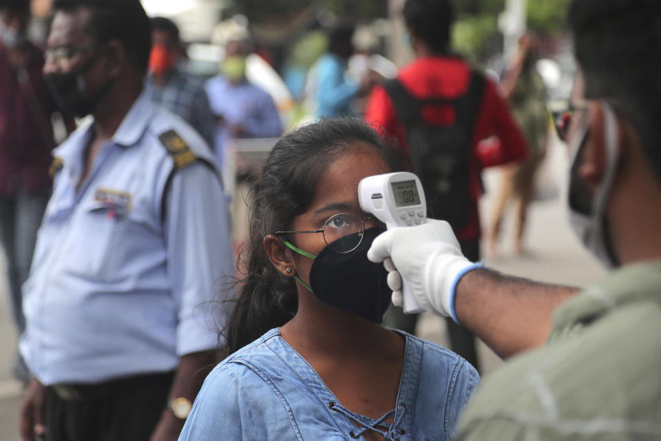 An official checks the body temperature of a candidate wearing a face mask as a precaution against coronavirus before appearing for National Eligibility cum Entrance Test ( NEET) at an exam centre in Hyderabad, India, Sunday, Sept. 13, 2020. NEET is for students who wish to study undergraduate medical and dental courses in government or private medical colleges in India. India's coronavirus cases are now the second-highest in the world and only behind the United States. (AP Photo/Mahesh Kumar A.)