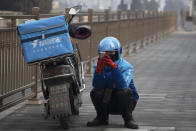 In this photo taken Tuesday, Feb. 11, 2020, a delivery man checks his phone while waiting on a street of Beijing, China. Millions of Chinese workers and entrepreneurs are bearing the rising costs of an anti-virus campaign that has shut down large sections of the economy. The government has imposed restrictions nationwide that have stalled travel and sales of real estate and autos. (AP Photo/Ng Han Guan)
