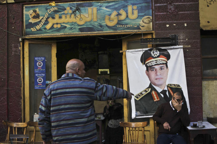 """FILE - In this Tuesday, Jan. 27, 2014 file photo, a man sits under a banner with the photo of Defense Minister Gen. Abdel-Fattah el-Sissi as he drinks his tea at the """"Al Mosheer Cafe"""" or """"Marshal Cafe"""" in Cairo, Egypt. The head of Egypt's military, Abdel-Fattah el-Sissi, is riding on a wave of popular fervor that is almost certain to carry him to election as president. Unknown only two years ago, a broad sector of Egyptians now hail him as the nation's savior after he ousted the Islamists from power, and the state-backed personality cult around him is so eclipsing, it may be difficult to find a candidate to oppose him if he runs. Still, if he becomes president, he faces the tough job of ruling a deeply divided nation that has already turned against two leaders. (AP Photo/Mohammed Abu Zaid, File)"""