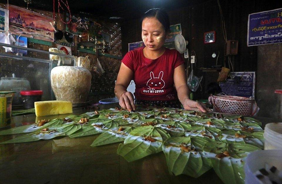 A hawker in Myanmar sells areca fruits wrapped in betel leaves, an addictive stimulant called 'betel nuts'. Photo: EPA-EFE