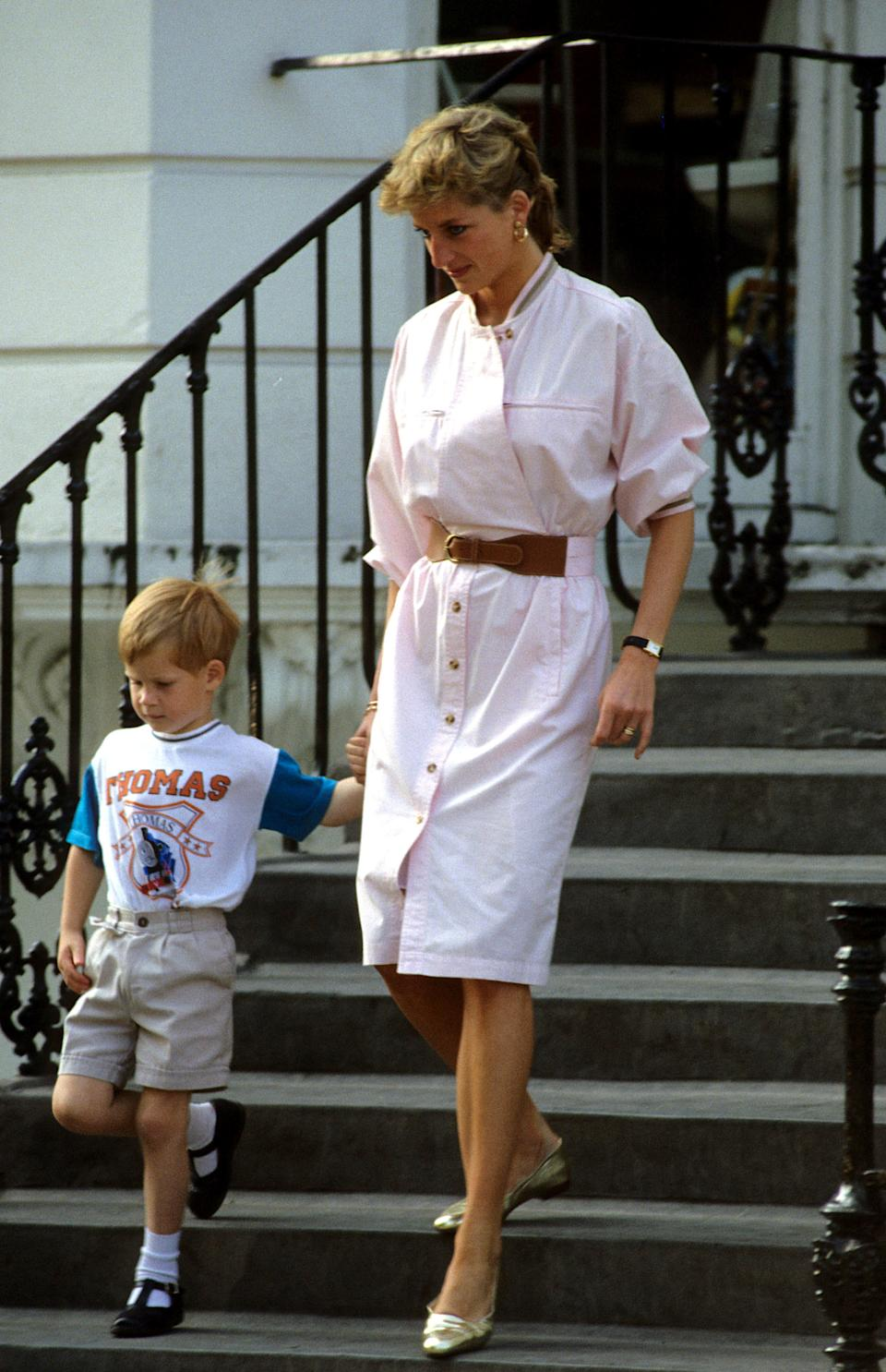 Prince Harry wears a Thomas the Tank Engine t-shirt when he leaves nursery school with his mother Diana, Princess of Wales in June 1989 in London.