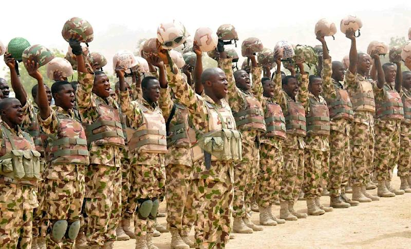 Picture released by State House Photo on February 26, 2015 shows soldiers fighting Boko Haram Islamists cheering Nigerian President Goodluck Jonathan on his arrival in Mubi, recently recaptured from insurgents (AFP Photo/Ho)