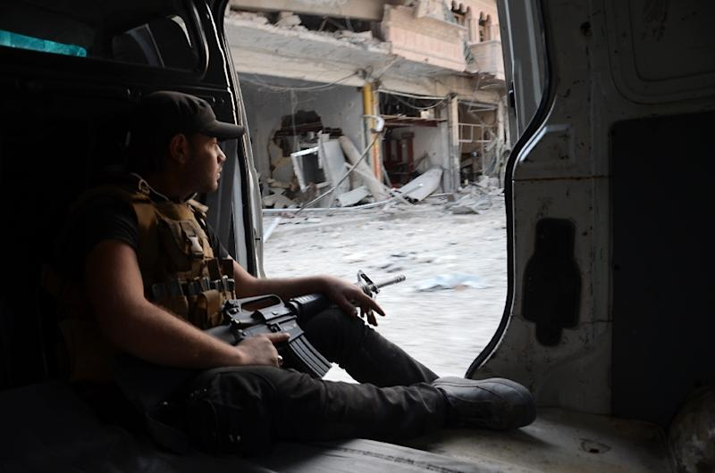 A Turkish-backed Syrian rebel sits in a vehicle in the northwestern border town of Al-Bab on February 23, 2017 after its capture from the Islamic State group