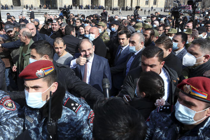Armenian Prime Minister Nikol Pashinyan, center, gestures as arriving at the main square in Yerevan, Armenia, Thursday, Feb. 25, 2021. Armenia's prime minister has spoken of an attempted military coup after facing the military's General Staff demand to step down. The developments come after months of protests sparked by the nation's defeat in the Nagorno-Karabakh conflict with Azerbaijan. (Hayk Baghdasaryan/PHOTOLURE via AP)