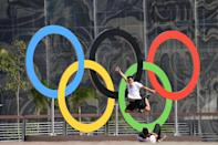 A man jumps in front of the Olympic rings at the Olympic park on July 31, 2016 in Rio de Janeiro ahead of the 2016 Rio Olympic Games (AFP Photo/Kirill Kudryavtsev)