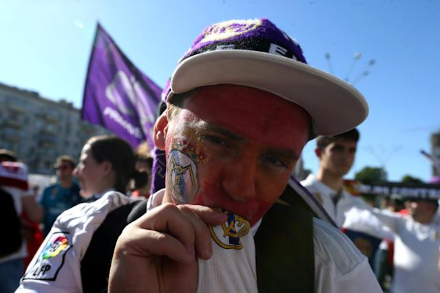 Soccer Football - Champions League Final - Real Madrid v Liverpool - Kiev, Ukraine - May 26, 2018 Real Madrid fan kisses the badge on his shirt before the match REUTERS/Viacheslav Ratynskyi