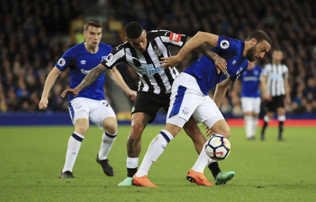Newcastle United's Kenedy, center, challenges Everton's Cenk Tosun, right, during the English Premier League soccer match between Everton and Newcastle United at Goodison Park, Liverpool, England, Monday, April 23, 2018. (Peter Byrne/PA via AP)