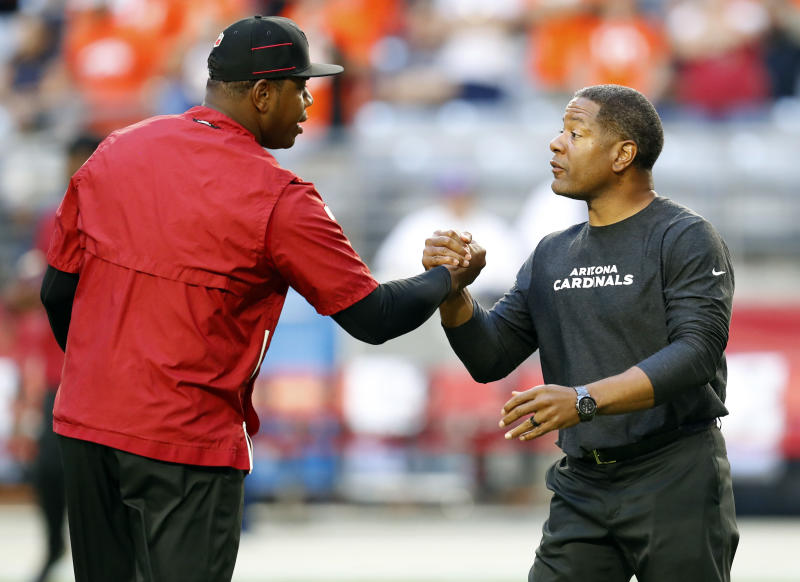 Arizona Cardinals quarterback coach Byron Leftwich, left, greets head coach Steve WIlks prior to an NFL football game against the Denver Broncos, Thursday, Oct. 18, 2018, in Glendale, Ariz. The Cardinals announced Friday, Oct. 19, 2018, that offensive coordinator Mike McCoy has been relieved of his duties and that Byron Leftwich will assume his position. (AP Photo/Ralph Freso)