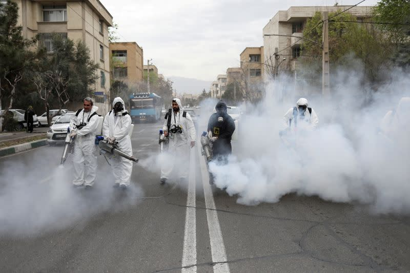 FILE PHOTO: Members of firefighters wear protective face masks, amid fear of coronavirus disease, as they disinfect the streets, ahead of the Iranian New Year Nowruz, March 20, in Tehran
