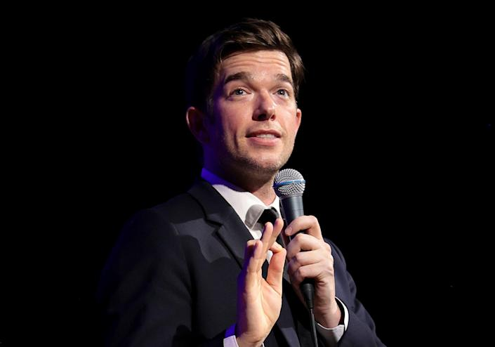 John Mulaney performing a stand-up in a gray suit