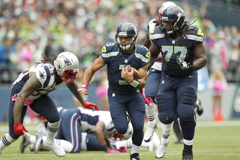 Seattle Seahawks quarterback Russell Wilson (3) carries the ball as teammate James Carpenter (77) blocks and New England Patriots linebacker Brandon Spikes, left, moves in for the tackle in the first half of an NFL football game, Sunday, Oct. 14, 2012, in Seattle. (AP Photo/Elaine Thompson)