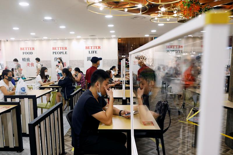People eat at tables installed with plexiglass dividers at a food court in Singapore as the city state reopens the economy amid the coronavirus disease (COVID-19) outbreak, June 19, 2020. REUTERS/Edgar Su