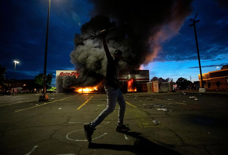 A man poses for a photo in the parking lot of an AutoZone store in flames, while protesters hold a rally for George Floyd in Minneapolis on Wednesday. (Photo: ASSOCIATED PRESS)