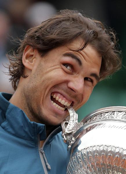 Spain's Rafael Nadal bites the cup after defeating compatriot David Ferrer in the men's final match of the French Open tennis tournament at the Roland Garros stadium Sunday, June 9, 2013 in Paris. Nadal won 6-3, 6-2, 6-3. (AP Photo/Michel Euler)