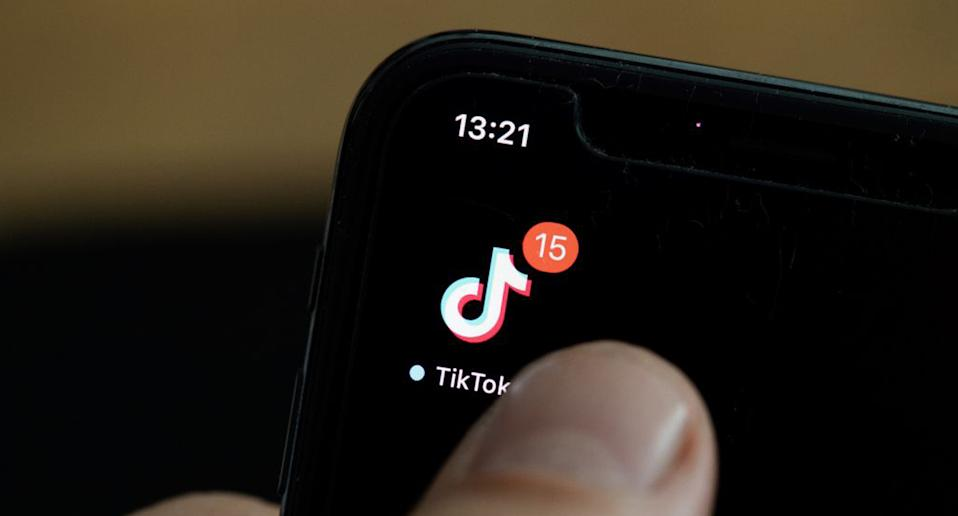 Pictured is a TikTok app icon on a smartphone.