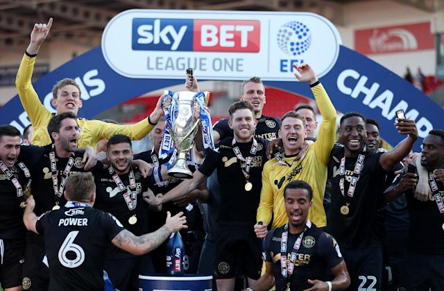 "Soccer Football - League One - Doncaster Rovers vs Wigan Athletic - Keepmoat Stadium, Doncaster, Britain - May 5, 2018 Wigan Athletic players celebrate with the trophy after winning League One Action Images/John Clifton EDITORIAL USE ONLY. No use with unauthorized audio, video, data, fixture lists, club/league logos or ""live"" services. Online in-match use limited to 75 images, no video emulation. No use in betting, games or single club/league/player publications. Please contact your account representative for further details."