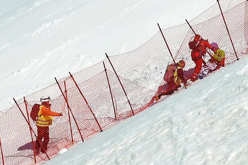 Medical staff take care of German Maria Hoefl-Riesch, right, after she crashed during the women's World Cup downhill race at the FIS Alpine World Cup finals, in Lenzerheide, Switzerland, Wednesday, March 12, 2014. (AP Photo/Keystone,Anna Suter)