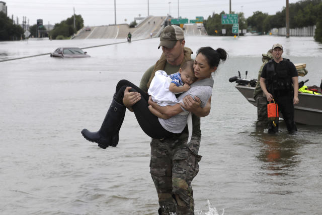 <p>Houston Police SWAT officer Daryl Hudeck carries Catherine Pham and her 13-month-old son Aiden after rescuing them from their home surrounded by floodwaters from Tropical Storm Harvey Sunday, Aug. 27, 2017, in Houston, Texas. (Photo: David J. Phillip/AP) </p>
