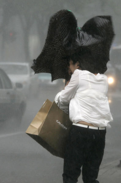 A woman walks in a rainstorm brought on by Typhoon Haikui Wednesday Aug. 8, 2012 in Shanghai, China. The typhoon slammed into eastern China's Zhejiang province early Wednesday, packing winds up to 150 kilometers (90 miles) per hour and triggering flooding. (AP Photo)