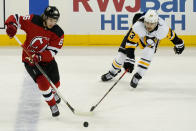Pittsburgh Penguins left wing Brandon Tanev (13) defends against New Jersey Devils center Jack Hughes (86) during the second period of an NHL hockey game Thursday, March 18, 2021, in Newark, N.J. (AP Photo/John Minchillo)