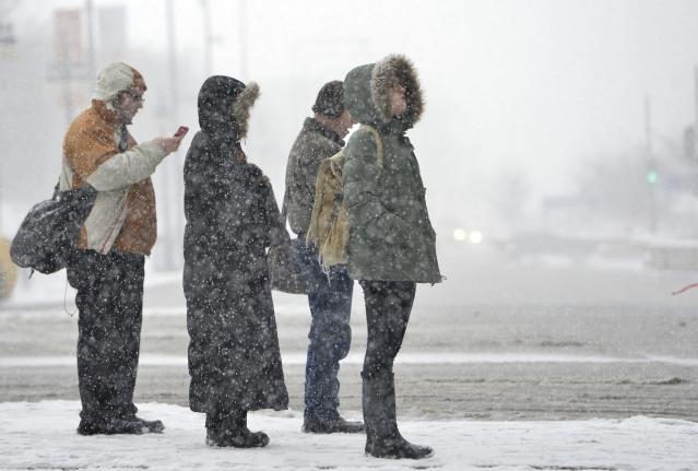 CHICAGO, IL - MARCH 5: Pedestrians wait to cross the street on March 5, 2013 in Chicago, Illinois. The worst winter storm of the season is expected to dump 7-10 inches of snow on the Chicago area with the worst expected for the evening commute. (Photo by Brian Kersey/Getty Images)