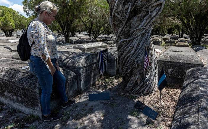 Miami, Florida, May 7 2021 - Retired Miami Detective Jerry Lynn Dellamico stands over makeshift memorials for City of Miami Officer Johnnie Young (right) and Metro Dade Officer Simmons Arrington at Evergreen Memorial Park in Allapatah.