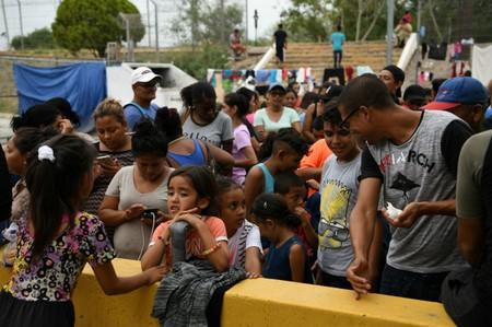 Migrants, many of whom are asylum seekers sent back to Mexico from the U.S. under Migrant Protection Protocols (MPP), line up for a free meal provided by volunteers in Matamoros