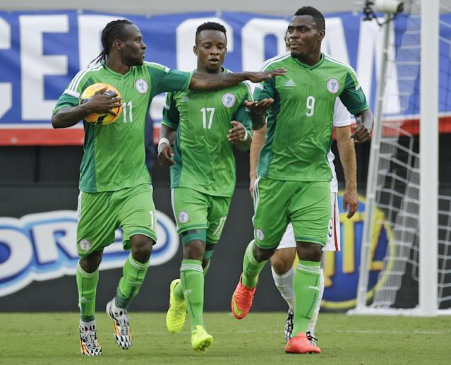 Nigeria's Victor Moses (11) is congratulated by teammates Ogenyi Onazi (17) and Emmanuel Emenike (9) after scoring a goal on a penalty kick against the United States during the second half of an international friendly soccer match in Jacksonville, Fla., Saturday, June 7, 2014. The United States won 2-1. (AP Photo/John Raoux)