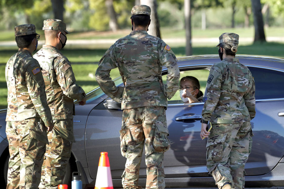 A lady speaks with National Guard solders prior to being tested for the COVID-19 Coronavirus Tuesday, July 28, 2020 at Cesar Chavez City Park in Phoenix. The two-week testing event is aimed at bringing tests to Phoenix's Laveen neighborhood, home to many Latinos and Blacks who have been disproportionately affected by the coronavirus. Latino leaders say governments need to do more to communicate effectively with Hispanic communities to ensure people know where to get tested and encourage them to participate. (AP Photo/Matt York)