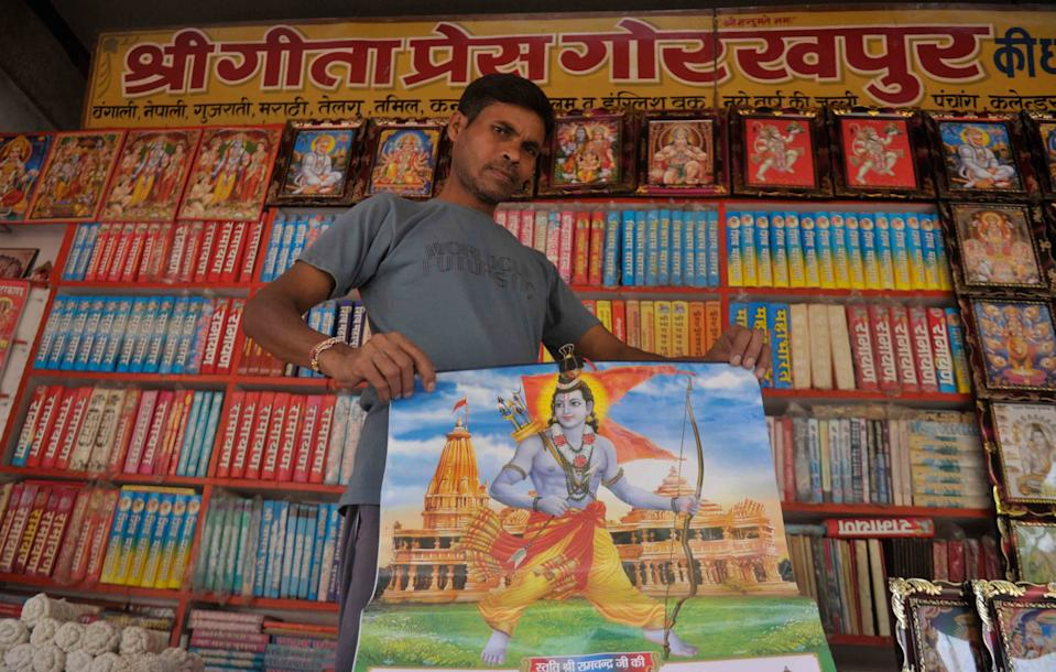 AYODHYA, INDIA - AUGUST 4: A vendor holds up a poster featuring the Hindu god Ram, on the eve of the foundation stone laying ceremony of the Ram Janmabhumi temple on August 4, 2020 in Ayodhya, India. Prime Minister Narendra Modi will on Wednesday attend a public function on laying of the foundation stone of 'Shree Ram Janmabhoomi Mandir' at Ayodhya. Ram Janmabhoomi Teerth Kshetra, the trust set up for the construction and management of Ram temple, has invited 175 eminent guests for the foundation stone-laying ceremony after personally discussing with BJP veterans L K Advani and Murli Manohar Joshi, lawyer K Parasaran and other dignitaries. (Photo by Deepak Gupta/Hindustan Times via Getty Images)