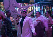 """This image released by Netflix shows Ewan McGregor, center, David Pittu, second right, and Rebecca Dayan, right, in a scene from """"Halston."""" (Atsushi Nishijima/Netflix via AP)"""