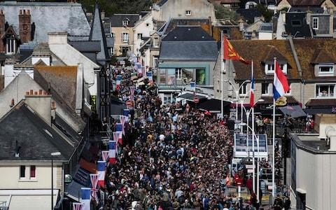 Visitors walk in a street of Arromanches in Normandy - Credit: AFP