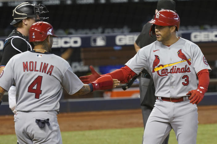 St. Louis Cardinals Yadier Molina (4) congratulates Dylan Carlson (3) after Carlson hit a grand slam in the ninth inning of a baseball game against the Miami Marlins, Wednesday, April 7, 2021, in Miami. The Cardinals defeated the Marlins 7-0. (AP Photo/Marta Lavandier)