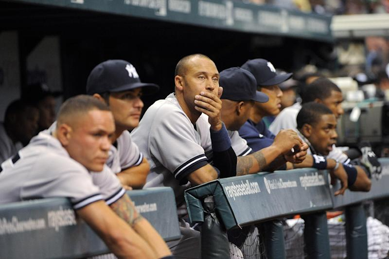 Members of the New York Yankees, including Derek Jeter, third from left, watch from the dugout during the ninth inning of a baseball game against the Tampa Bay Rays, Sunday, April 8, 2012, in St. Petersburg, Fla. The Rays won 3-0. (AP Photo/Brian Blanco)