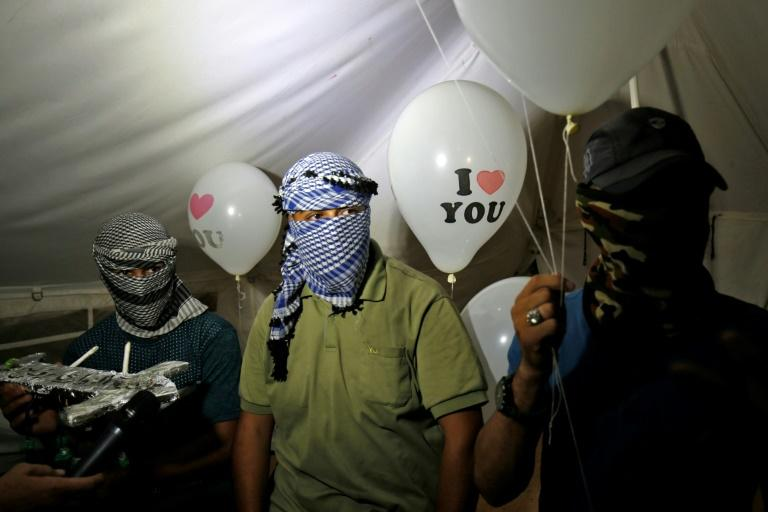 Masked Palestinian protesters hold incendiary devices attached to ballons to be flown towards Israel, near the border east of Rafah in the southern Gaza Strip, on September 26, 2018