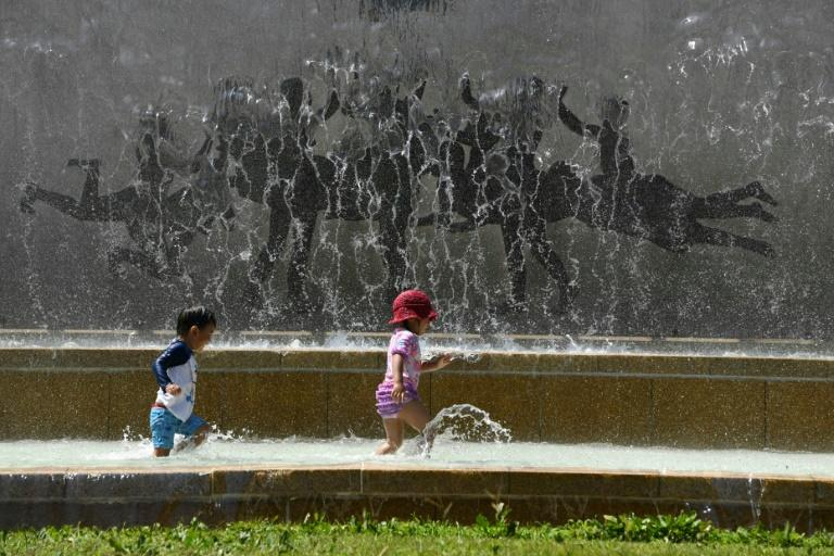 Children play in a water fountain in a Tokyo park