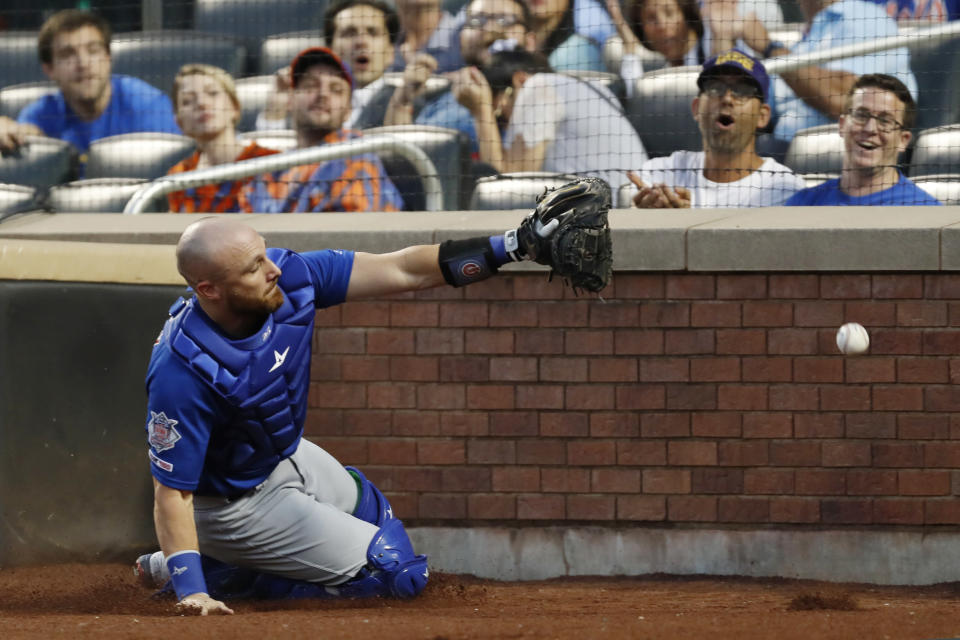 Chicago Cubs' catcher Jonathan Lucroy slides into the wall behind home plate as he tries catch to catch New York Mets' Pete Alonso's pop fly during the first inning of a baseball game Thursday, Aug. 29, 2019, in New York. (AP Photo/Kathy Willens)