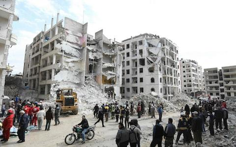 Syrian onlookers gather around rescue teams clearing the rubble in the morning of April 10, 2018 at the site of an explosion in the northwestern city of Idlib. - Credit: AFP