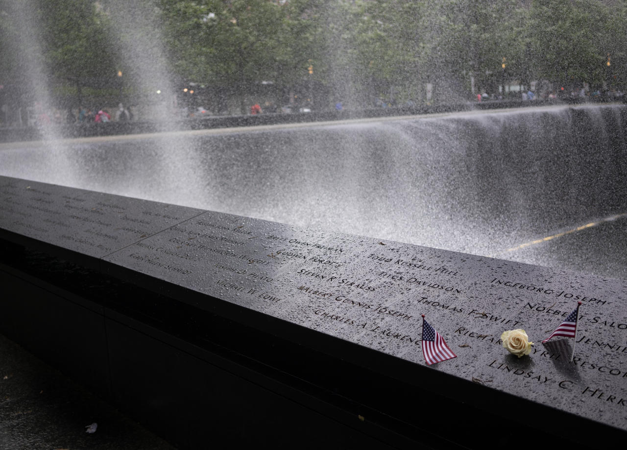 Wind sprays mist over the rim of the South Pool of the 9/11 Memorial Sunday, May 27, 2018, in New York. Roses are placed,by the 9/11 Memorial, on the names of those memorialized marking their birthdays. (AP Photo/Craig Ruttle)