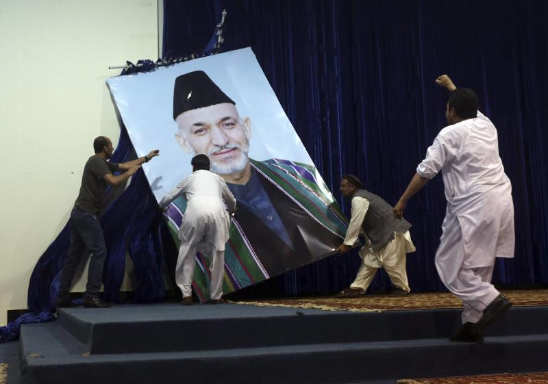Supporters of Afghan presidential candidate Abdullah Abdullah take down a large portrait of Afghan President Hamid Karzai before a gathering in Kabul