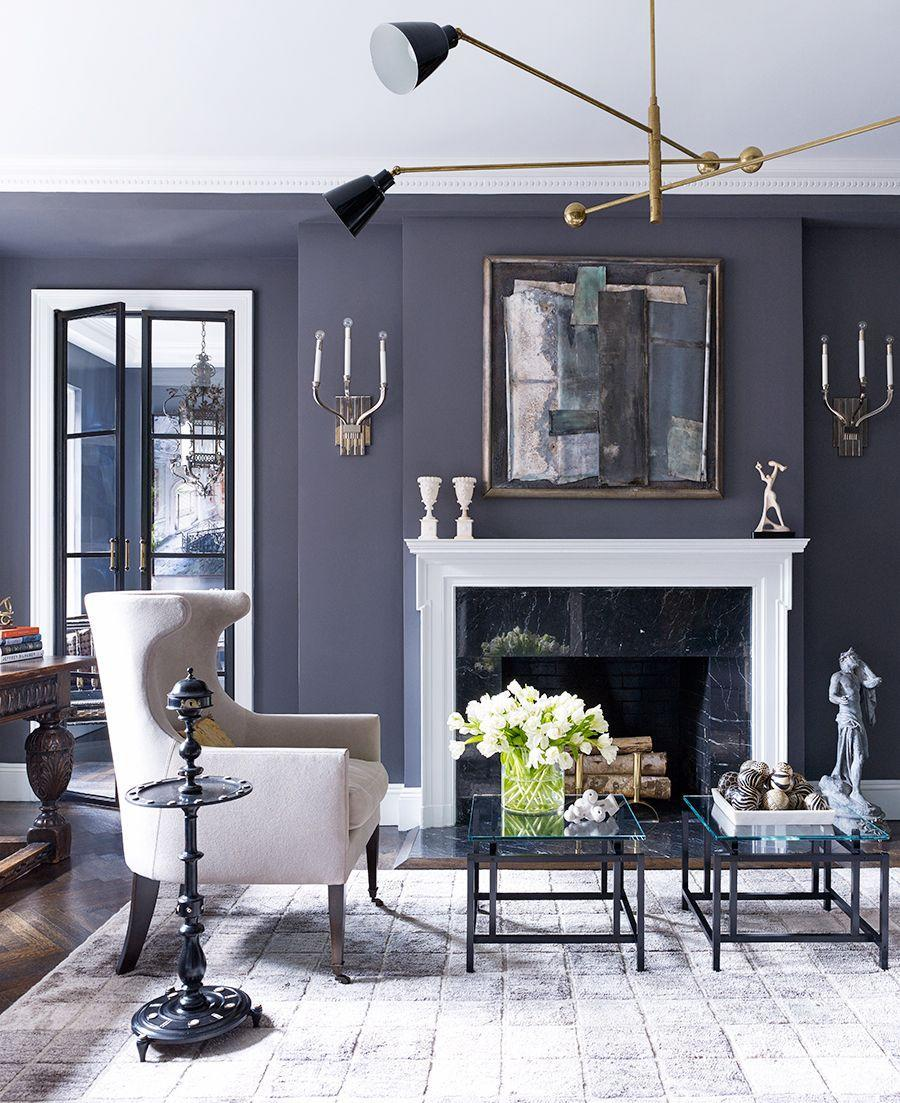 """<p>The traditional, neutral furniture in this room designed by <a href=""""https://www.balsamoantiques.com/"""" rel=""""nofollow noopener"""" target=""""_blank"""" data-ylk=""""slk:Balsamo Antiques and Interior Design"""" class=""""link rapid-noclick-resp"""">Balsamo Antiques and Interior Design</a> make a minimal visual impact so the moody colors, artwork, light fixtures, and other decorative accents can stand out. A deep, almost purple-gray tone turns out to be a wonderfully complex and evocative backdrop, so don't be afraid to try something different. </p>"""