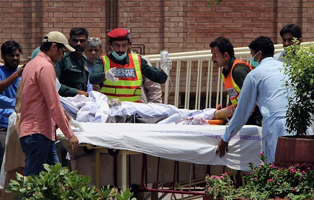 <p>Pakistani rescue worker and hospital staff transport a victim of an oil tanker explosion at a hospital in Multan, Pakistan, Sunday, June 25, 2017. An overturned oil tanker burst into flames in Pakistan on Sunday, killing scores of people who had rushed to the scene of the highway accident to gather leaking fuel, an official said. (AP Photo/Adeel Khan) </p>