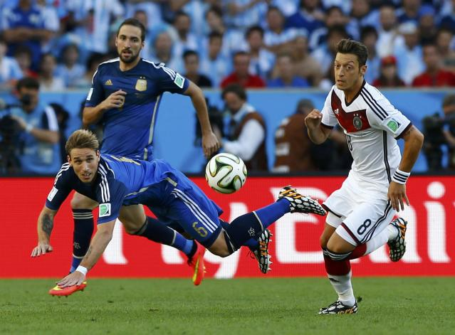 Germany's Mesut Ozil (R) fights for the ball with Argentina's Lucas Biglia (front) and Enzo Perez during their 2014 World Cup final at the Maracana stadium in Rio de Janeiro July 13, 2014. REUTERS/Darren Staples (BRAZIL - Tags: SOCCER SPORT WORLD CUP)
