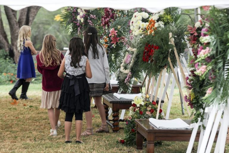 Girls attend the wake of women and children killed in an attack authorities have blamed on a drug cartel