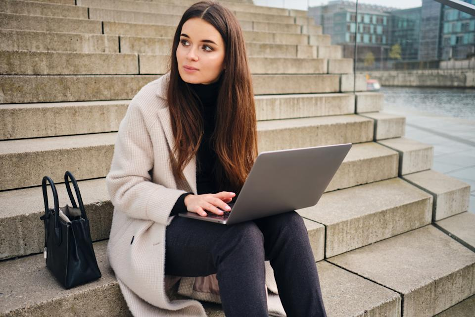 Young stylish businesswoman working on laptop sitting on stairs outdoor