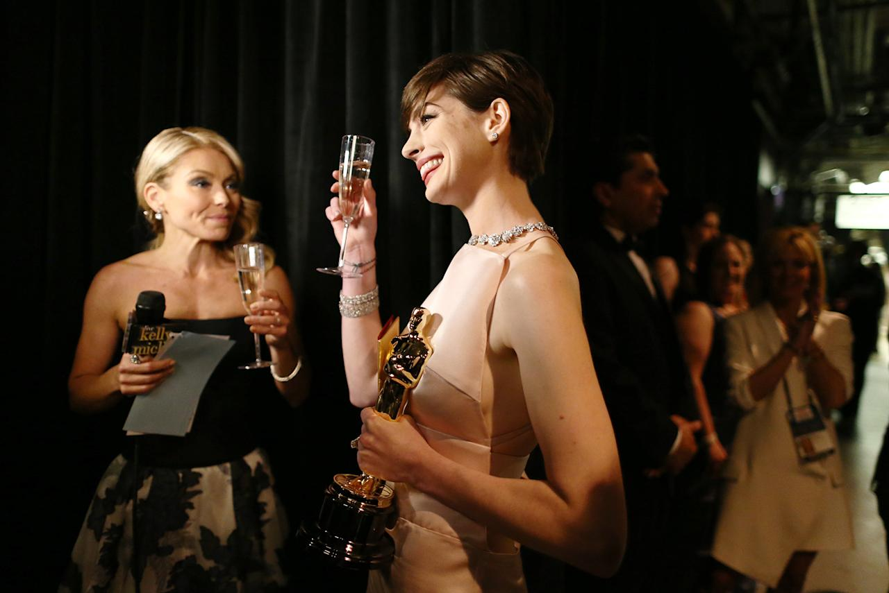"Anne Hathaway (R), winner of the Best Supporting Actress award for ""Les Miserables,"" and TV personality Kelly Ripa backstage during the Oscars held at the Dolby Theatre on February 24, 2013 in Hollywood, California."