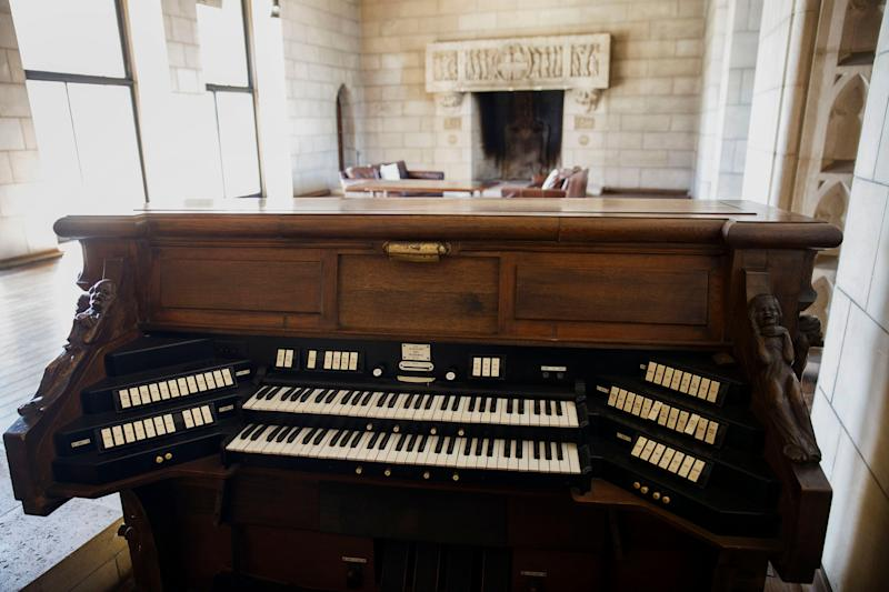 A pipe organ keyboard stands in a room that once housed a chapel.