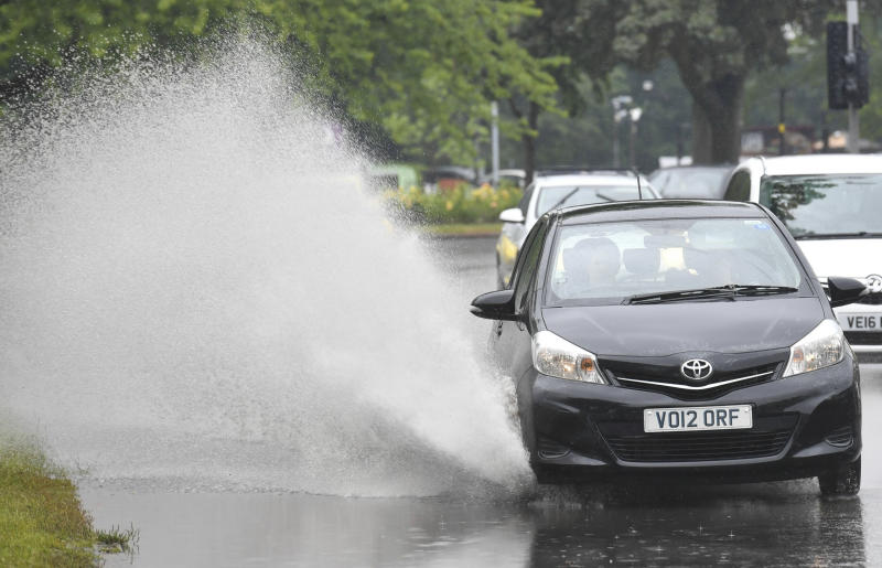 A car is driven through a puddle in Birmingham, England, as the weather across the UK changes with the arrival of Storm Miguel, Friday June 7, 2019. Periods of diluvial rains are inflicting localised flooding in some areas across the country. (Jacob King/PA Wire( / PA via AP)