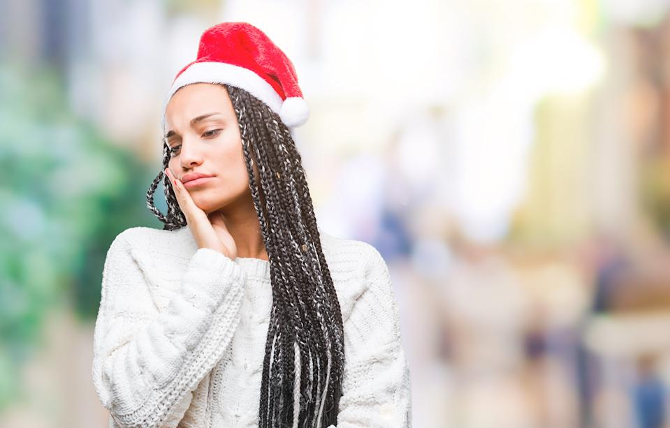 Young braided hair african american girl wearing christmas hat over isolated background thinking looking tired and bored with depression problems with crossed arms.